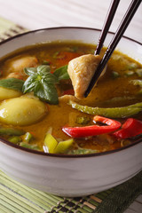 Thai green curry with chicken in a bowl macro. vertical