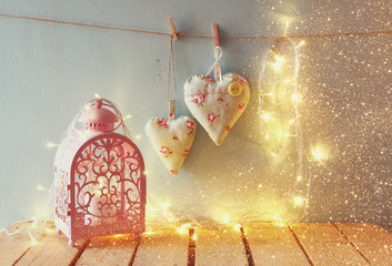 low key image of vintage pink classical frame, fabric hearts hanging on the rope and lantern with garland lights, on wooden table. retro filtered image with glitter overlay