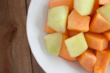closeup melon slice in white dish with wood table background
