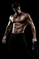Muscular man bodybuilder. Man posing on a black background, show