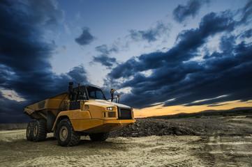 Großer Muldenkipper auf Baustelle mit düsteren Abendwolken