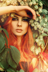 Fresh portriat of sexy redhair lady in leaves with wreath of hop