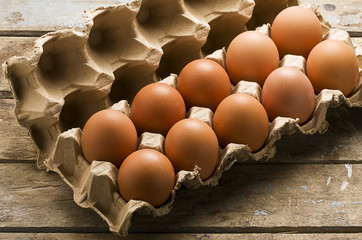 Ten whole brown eggs in a open cartoon container on rustic wooden table