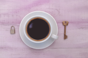 Closeup picture of cup of coffee with lock and key as symbol
