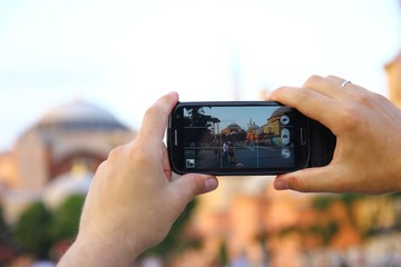 taking a photo with his phone in Istanbul