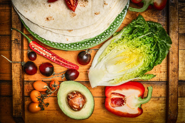 Tacos or burrito making with fresh vegetables on rustic wooden background