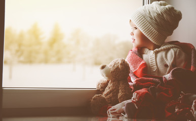 child little girl with  teddy bear at window and looking at wint
