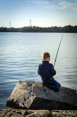 Small boy fishing from sea coast