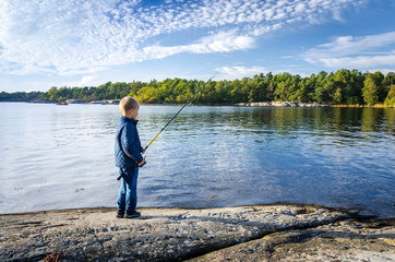 Small boy fishing in the sea