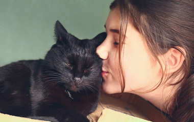 teen pretty girl kiss black cat close up portrait