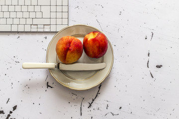 Two peaches in plate on office tabble, top view