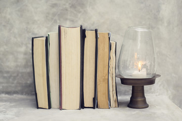 Different books and a candle on a table
