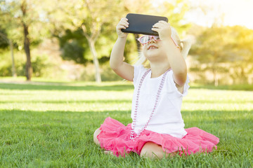Little Girl In Grass Taking Selfie With Cell Phone