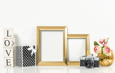 Golden picture frames, rose flowers and vintage camera. Product