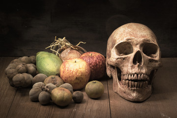 old skull and fruit still life on wooden board