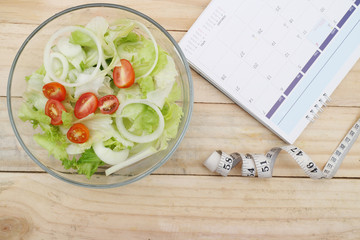 healthy eating, dieting, slimming and weigh loss concept - close up of salad, measuring tape
