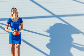 Smiling girl in blue holding a pumpkin with copy space