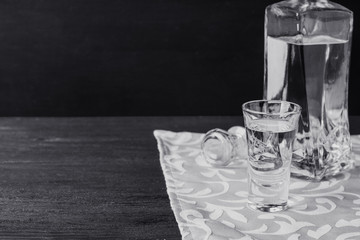 Bottle of vodka with glasses on the wooden table. Black and white image.