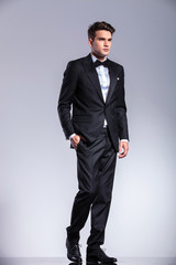 Tall young business man walking on studio background.