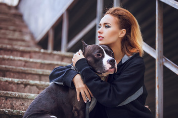 modern punk fashion, portrait of a beautiful model posing with American staff terrier over street background