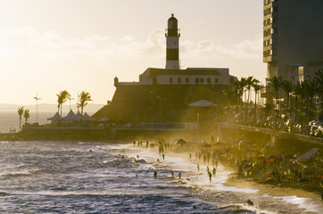 Portrait of the Farol da Barra Salvador Brazil lighthouse silhouette with misty waves at golden sunset