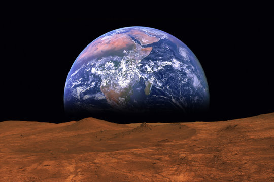 Imaginary view of earth rising from the horizon of plant Mars. Elements of this image are furnished by NASA