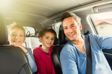 father with beard is talking with his two kids in the car