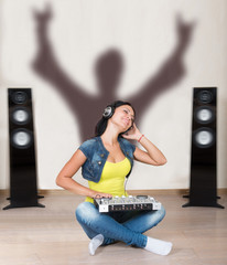 Woman in headphones with dj mixer sitting on the floor