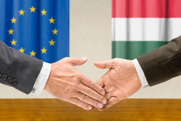 Vertreter der EU und Ungarns reichen sich die Hand
