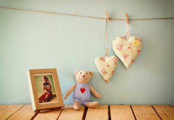 teddy bear over wood table next to photo frame and fabric hearts. retro filtered image