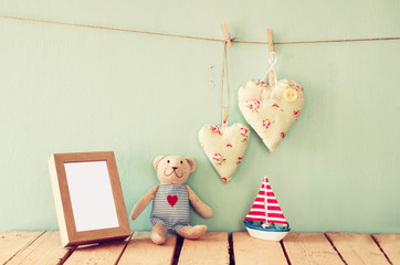 wooden boat toy and teddy bear over wood table next to photo frame  and fabric hearts. retro filtered image