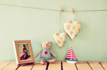 wooden boat toy and teddy bear over wood table next to photo frame with kid's old photography and fabric hearts. retro filtered image