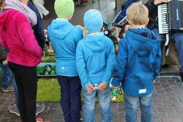 Kinder hören einem Straßenmusiker zu