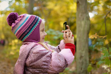 Little girl making photo or video with smartphone in the forest. Selective focus with shallow depth of field.
