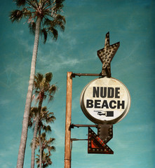 aged and worn vintage photo of nude beach sign with palm trees