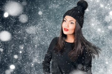 Beautiful asian woman wearing knitted hat with pompom in a snow.