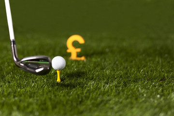 Targeting money with golf club and ball on green grass
