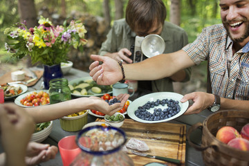 A group of friends gathered at a table outdoors, sharing dishes of fresh fruits and salads.