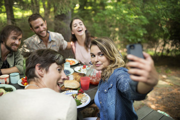 A picnic in woodland. Friends seated around a table, one woman taking a selfie of the group.