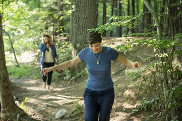 Two women walking down a woodland path.