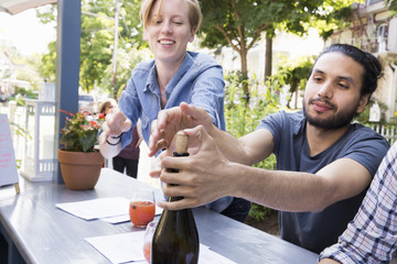Young man and woman outdoors at a cafe, one trying to recork a bottle of wine.