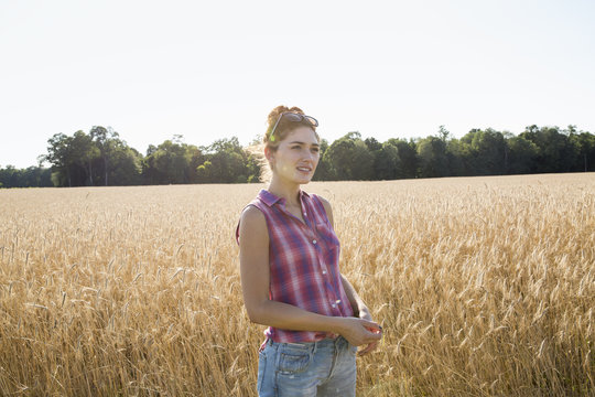 Young woman wearing a checkered shirt standing in a cornfield.