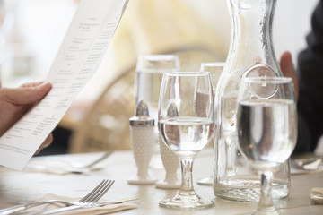 Close up of wine and water glasses and place settings at a table in a restaurant. A person's hand holding the menu.