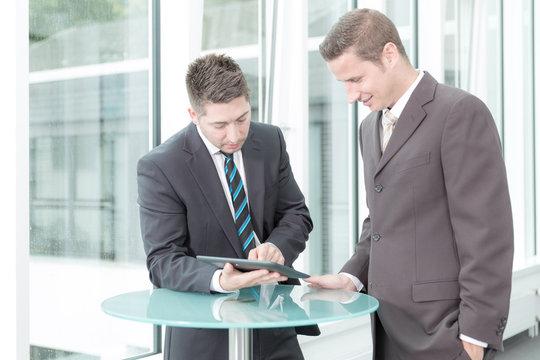 Zwei Geschäftsleute bei einer Besprechung am Stehtisch