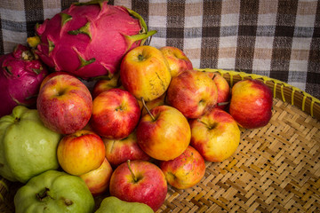 low key image of red apples over wodden textured table
