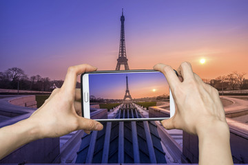 Girl taking pictures on mobile smart phone in eiffel tower, Pari