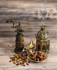 Still life with vintage oriental latern and mill. Raisins and da