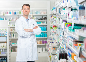 Confident Pharmacist Standing Arms Crossed In Pharmacy