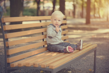 Adorable baby sitting on the bench