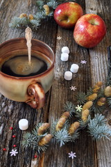 Large cup of hot coffee, red apples and pine branches